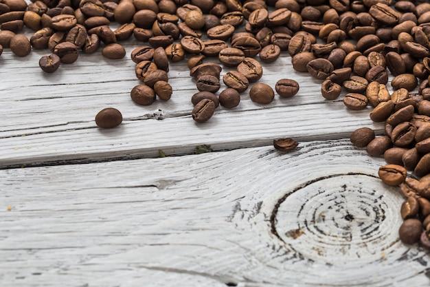 Grains De Café Sur Un Mur En Bois Blanc, Gros Plan Photo gratuit