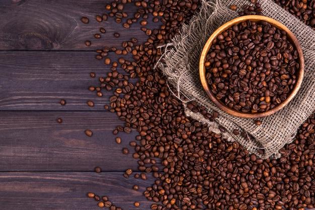 Grains de café torréfiés dans un bol sur un fond en bois foncé Photo Premium
