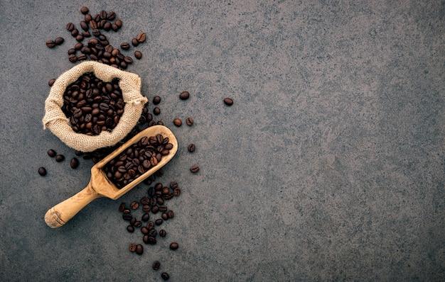 Grains de café torréfiés foncés sur pierre. Photo Premium