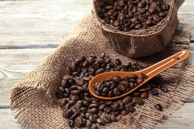 Grains de café torréfiés sur un plancher en bois Photo Premium