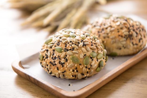 Grains de céréales sains multigrains mélangés pain en plaque de bois Photo Premium