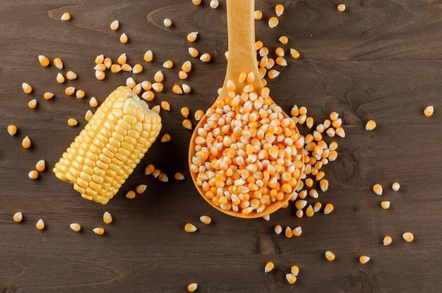 Grains De Maïs Avec Une Tranche D'épi Dans Une Cuillère En Bois Sur Une Table En Bois, Mise à Plat. Photo gratuit
