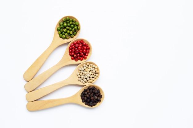 Grains de poivre vert, rouge blanc et noir avec une cuillère en bois sur blanc Photo Premium