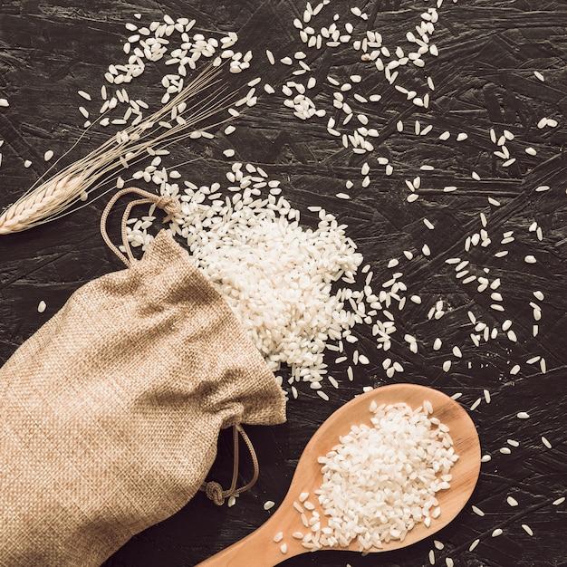 Grains de riz sur le sac avec une cuillère en bois Photo gratuit
