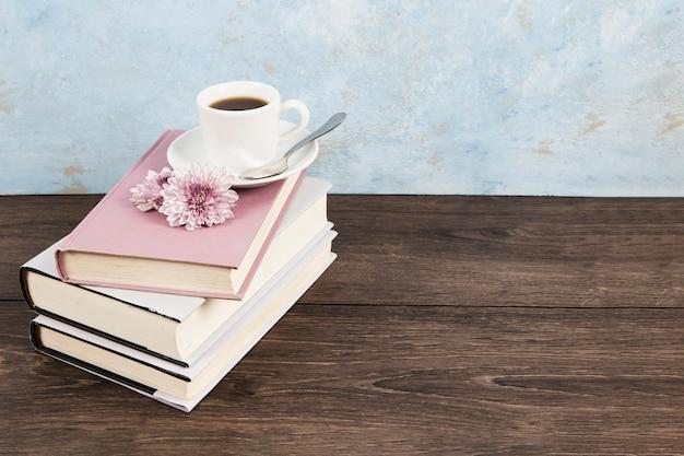 Grand angle d'un café sur des livres Photo gratuit