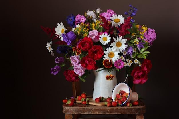 Grand bouquet de fleurs d'été de jardin dans un pot et des fraises sur un fond sombre. Photo Premium