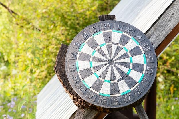 Un grand cercle noir de fléchettes sur un fond d'herbe verte par une chaude journée d'été Photo Premium
