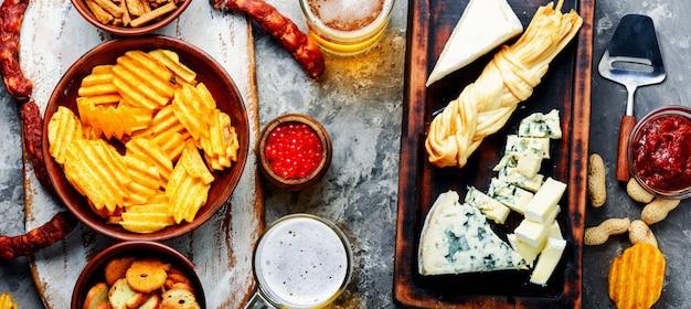 Grand choix de snacks à la bière. ensemble de fromages, poisson, frites et snacks Photo Premium