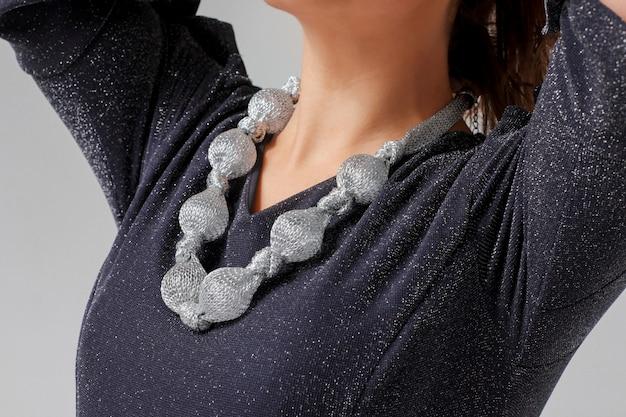 Grand collier argenté original sur jeune femme en veille bleu brillant Photo Premium