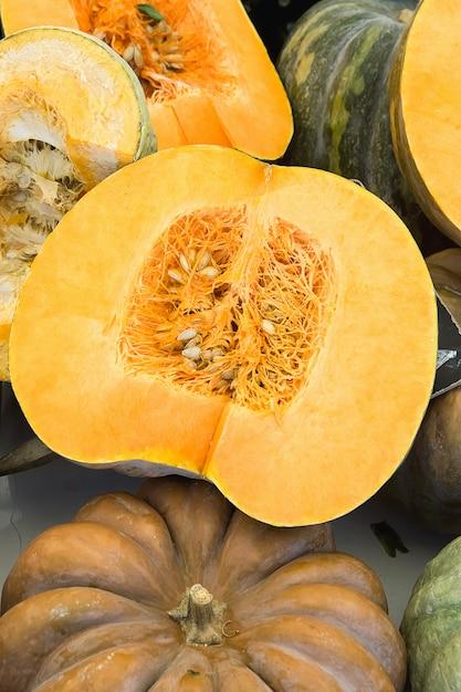 Grand coloré belles citrouilles orange foncé et vert foncé entières et coupées en deux. Photo Premium