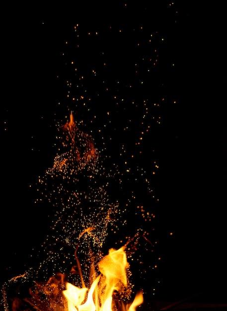 Grand feu allumé avec flammes et étincelles orange qui volent dans différentes directions Photo Premium