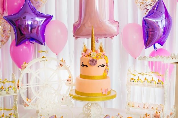 Un Grand Gâteau Et Beaucoup De Bonbons Dans La Salle Lumineuse Décorée De Boules Gonflables Photo Premium