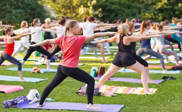 Grand Groupe D'adultes Assistant à Un Cours De Yoga à L'extérieur Dans Le Parc Photo Premium