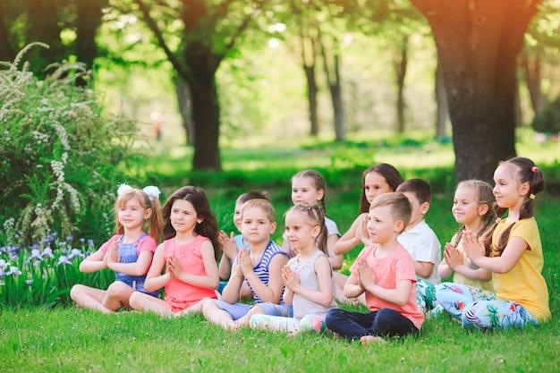 Un Grand Groupe D'enfants Pratiquant Le Yoga Dans Le Parc Assis Sur L'herbe. Photo Premium