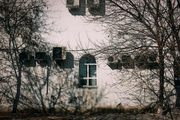 Un grand immeuble d'habitation montrant des signes de temps avec des unités de climatisation suspendus à l'extérieur. Photo Premium