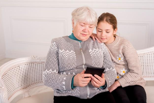 Grand-mère âgée lisant avec sa petite-fille Photo gratuit