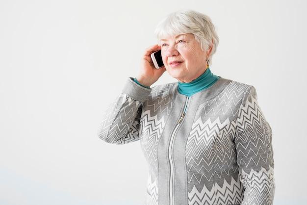 Une grand-mère âgée parlant par téléphone Photo gratuit