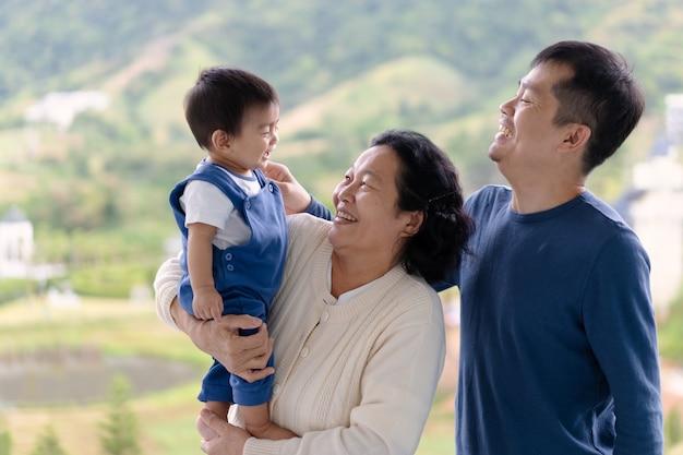 La Grand-mère Asiatique Tient Le Petit-fils Du Petit Garçon Et Le Garçon Qui Rit Avec Son Père. Photo Premium