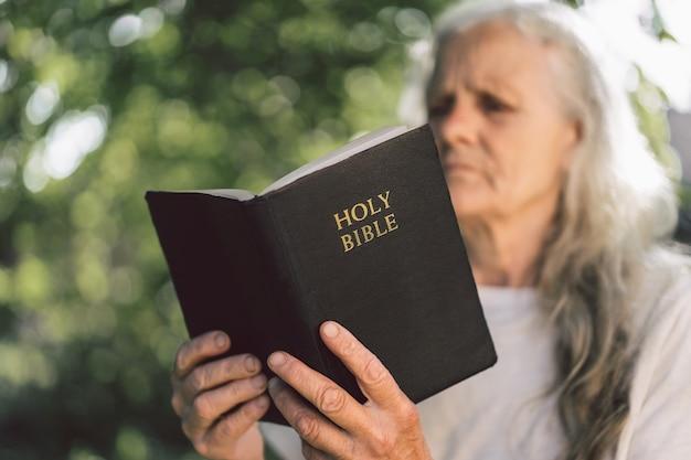 La Grand-mère Aux Cheveux Gris Tient La Bible Dans Ses Mains. Photo Premium