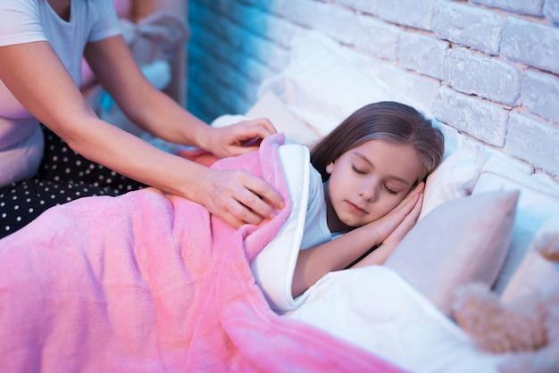 Grand-mère cajoler sa petite-fille pour dormir la nuit à la maison Photo Premium