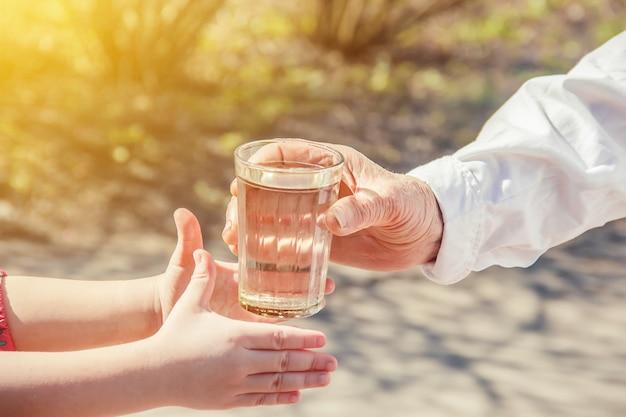 Grand-mère donnant un verre d'eau propre à un enfant. mise au point sélective. Photo Premium