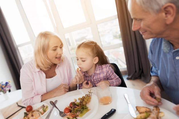La grand-mère est assise à la table et nourrit sa petite-fille. Photo Premium