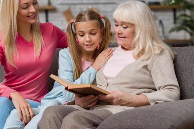 Grand-mère Et Famille Assis Sur Un Canapé Et Lire Un Livre Photo gratuit