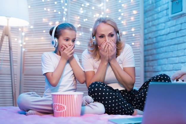 Grand-mère avec une fille sont choqués en regardant un film la nuit Photo Premium