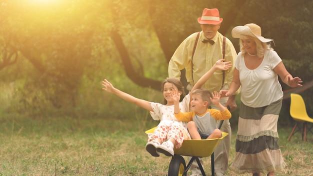 Grand-mère et grand-père poussent leurs petits-enfants dans une brouette Photo Premium