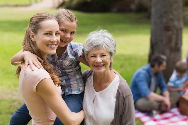 Grand-mère, mère et fille avec la famille en arrière-plan au parc Photo Premium