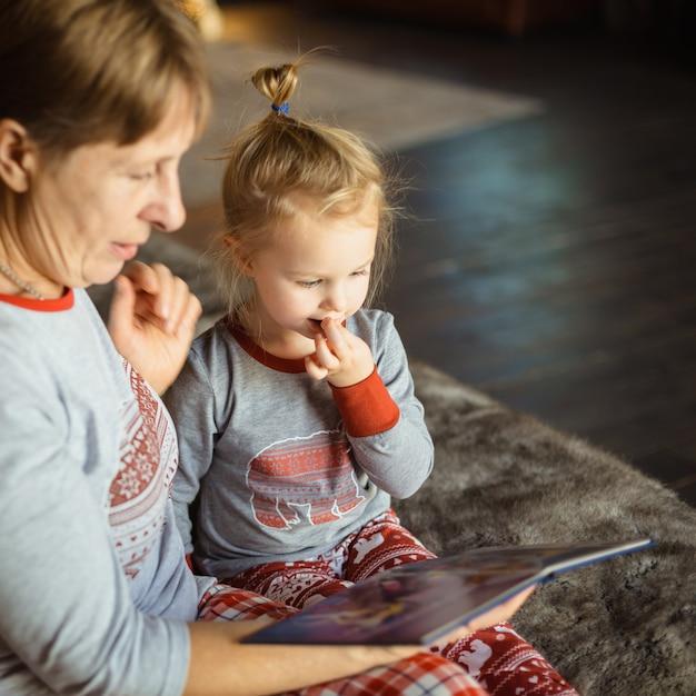 Grand-mère Et Petite-fille S'amusent Ensemble En Lisant Un Livre Sur Le Lit. Photo Premium