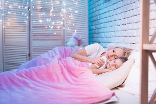 Grand-mère et petite-fille sont couchées dans leur lit la nuit. Photo Premium