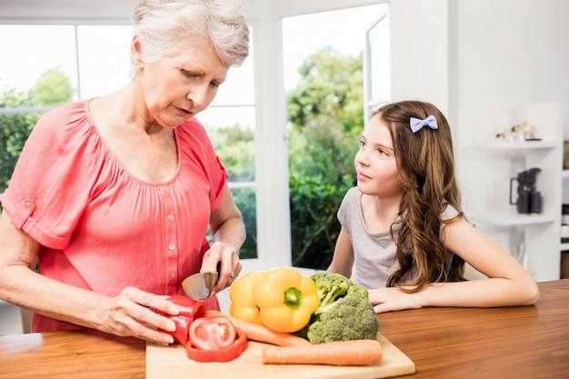Grand-mère Et Petite-fille Trancher Des Légumes Dans La Cuisine Photo Premium