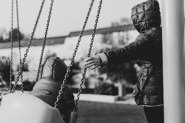Grand-mère secoue son petit-fils sur une balançoire Photo Premium