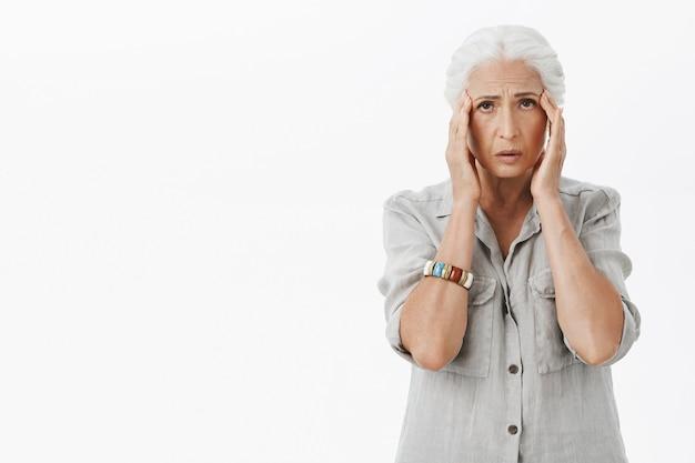 Grand-mère Triste épuisée Touchant La Tête, Se Plaignant De Maux De Tête, Migraine Photo gratuit