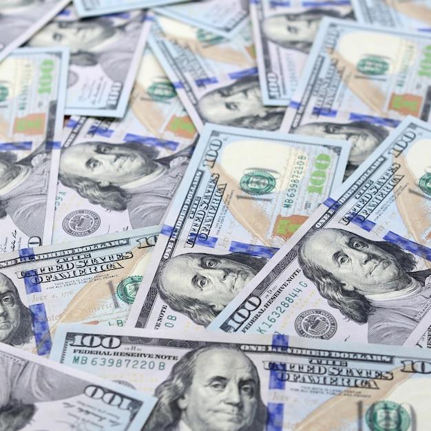 Un grand nombre de billets en dollars américains d'un nouveau modèle avec une bande bleue au milieu. vue de dessus Photo Premium