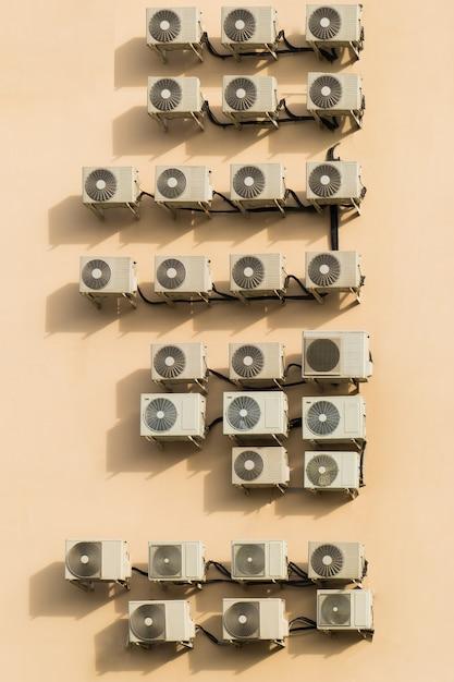 Un grand nombre de climatiseurs sur le mur marron Photo Premium