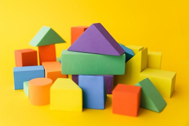 Un grand nombre de formes géométriques différentes multicolores et de formes différentes sur un fond jaune Photo Premium