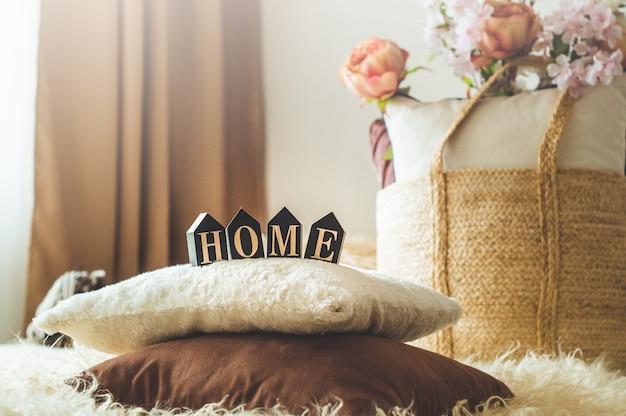 Un Grand Nombre D'oreillers Décoratifs Confortables Et L'inscription Home. à L'intérieur De La Maison Sur Le Lit Avec Un Panier En Osier Et Des Fleurs. Le Printemps à L'intérieur De La Maison. Concept De La Maison Photo Premium