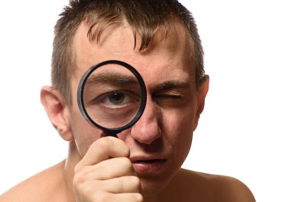 Grand Oeil Ouvert. Un Homme Tient Une Loupe Près De Son Visage. Chercher. Blanc Photo Premium