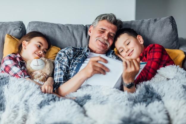 Grand-père allongé avec ses petits-enfants sur un canapé confortable avec le livre, lisant et racontant une histoire de conte de fées. les garçons et les filles l'écoutent. Photo Premium