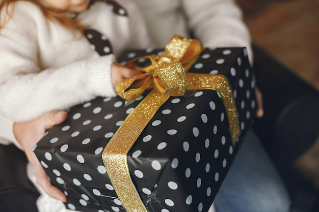 Grand-père Assis Avec Sa Petite-fille. Célébrer Noël Dans Une Maison Chaleureuse. Homme Dans Un Pull En Tricot Blanc. Photo gratuit