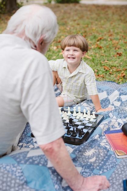 Un grand-père enseigne les petits échecs Photo gratuit