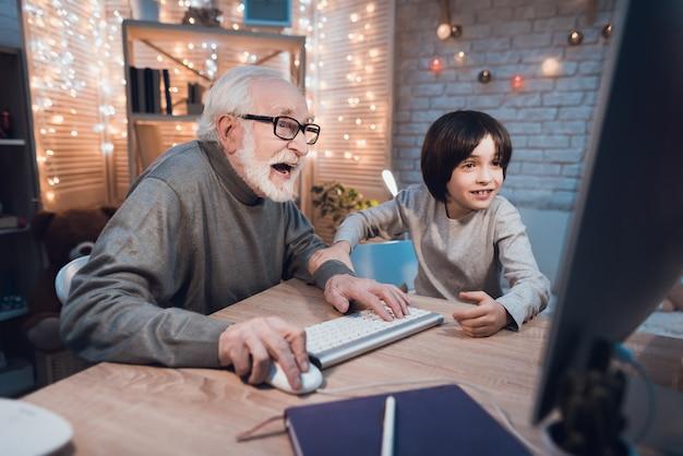 Grand-père Jouant à Des Jeux Informatiques Avec Petit-fils Photo Premium