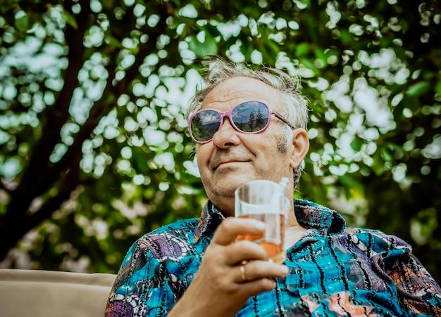 Grand-père Moderne Aime La Vie Avec Un Verre De Boisson à La Main Photo Premium