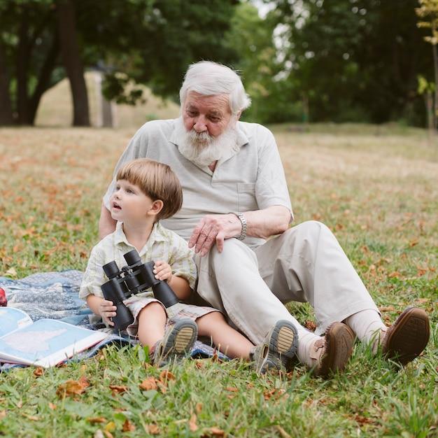 Grand-père Et Petit-fils Dans Un Parc Avec Des Jumelles Photo gratuit