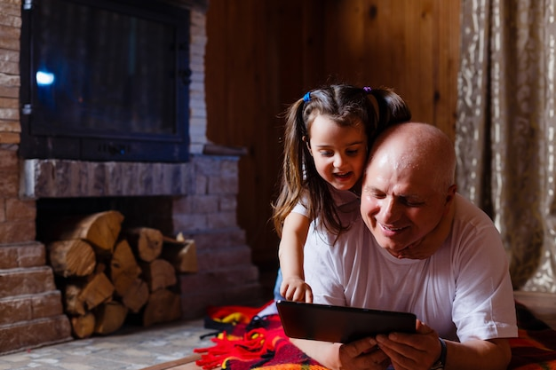 Grand-père et petite-fille avec tablette d'une maison près de la cheminée Photo Premium