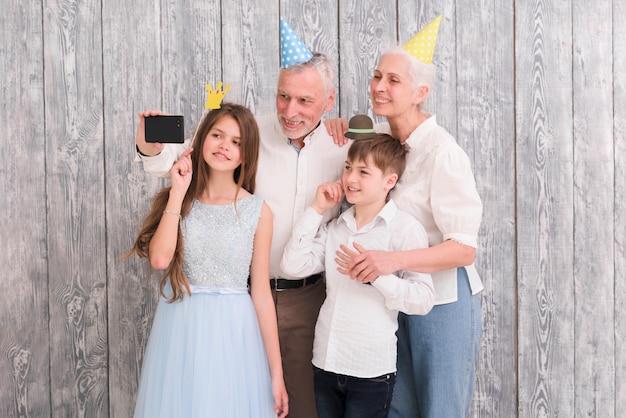 Grand-père prenant selfie sur téléphone mobile avec sa femme et ses petits-enfants à l'aide d'accessoires Photo gratuit