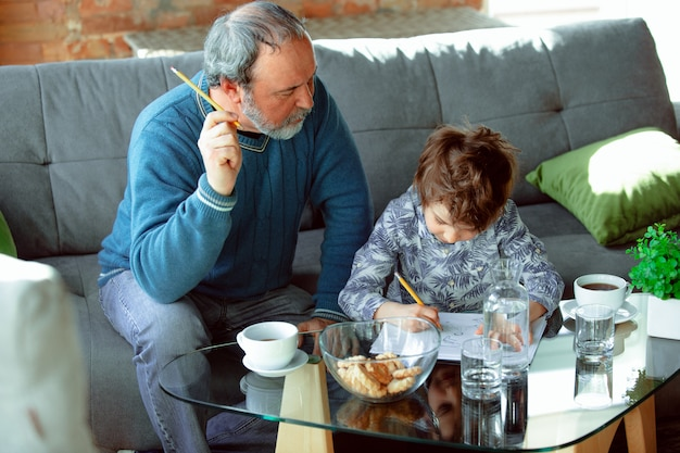 Grand-père Et Son Petit-fils Passent Du Temps Isolés à La Maison, étudient Photo gratuit