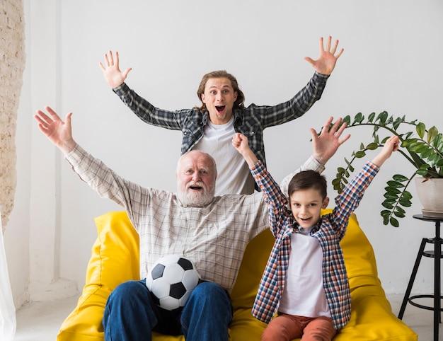 Grand-père avec son petit-fils et son fils se réjouissent de regarder le football Photo gratuit